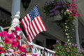 American flag on house porch the railing of a with flower baskets Stock Image