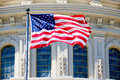 The American Flag waves in fron of the Capitol building Royalty Free Stock Photo