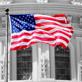 The American Flag waves in fron of the Capitol building in Washi Royalty Free Stock Photo