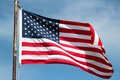 American flag on windy day an blowing in the wind a bright sunny Stock Photography