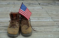 American flag in work boots brown with on a wooden deck Stock Images