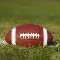American football on the field with green grass Royalty Free Stock Photos