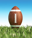 American football on the grass close up with blue sky at background no clouds side view from ground level with foreground out of Royalty Free Stock Photo