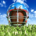American football helmet over the oval ball on the grass frontal close up view from ground level with sky and fluffy clouds Stock Photos