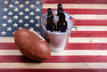 American football and ice cold beer on rustic wooden USA flag Royalty Free Stock Photo