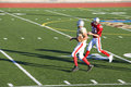 American football player chasing opposing receiver with ball during competitive game side view Royalty Free Stock Images