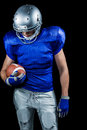 American football player looking down while holding ball Royalty Free Stock Photo