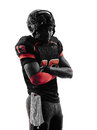 American football player standing arms crossed silhouette one in shadow on white background Royalty Free Stock Photo