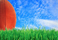 American football (rugby ball) on green grass over blue sky Royalty Free Stock Photo