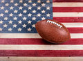 American football on rustic wooden USA flag Royalty Free Stock Photo