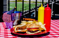 American football tailgating meal with cheeseburger hot dog potato chips hamburger patties hot dog wieners mustard and ketchup Royalty Free Stock Images