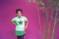 American girl african girls shows off her bright green clothes and fashion sense on a pink background Stock Image