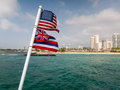 American and hawaiian flags off the back of a boat looking towards waikiki Stock Photography