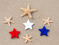 American holidays background with starfishes and color stars on the sand Royalty Free Stock Images