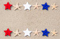 American holidays background with starfishes and color stars on the sand Royalty Free Stock Photo