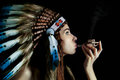 American indian girl smoking a pipe on black background Royalty Free Stock Image
