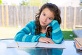 American latin teen girl doing homework on backyard relaxed table Royalty Free Stock Image