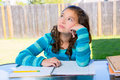 American latin teen girl doing homework on backyard relaxed table Stock Photography
