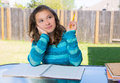 American latin teen girl doing homework on backyard thinking with pencil Royalty Free Stock Photos