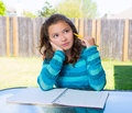 American latin teen girl doing homework on backyard thinking with pencil Royalty Free Stock Photography