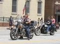 American legion riders in parade in small town america herman post a summer while a crowd watches on and an old brick building is Stock Image