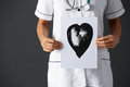 American nurse holding ink drawing of heart Stock Photo