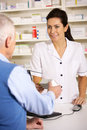 American pharmacist dispensing to senior man Stock Photo
