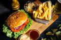 american stylish beef burger with grilled meat and mayo served with fries, coleslaw and beer Royalty Free Stock Photo
