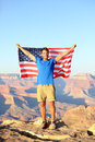 American usa flag tourist in grand canyon happy young man hiking and cheering at south rim during summer holidays Stock Photography
