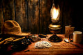 American west legend cowboy hotel room table scene worn hat atop gloves and gun in holster on an old western wood nightstand with Royalty Free Stock Photo