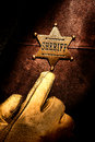 American west legend sheriff badge finger pointing lawman with his and hand wearing an old western glove to his on his chest to Royalty Free Stock Photo