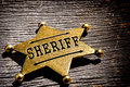 American west legend sheriff deputy star badge law enforcement officer antique shape gold color brass as vintage western lawman Royalty Free Stock Photos