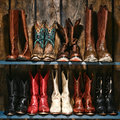 American west rodeo cowboy and cowgirl boots shelf used worn leather collection stacked on old wood in a ranch barn Stock Photo