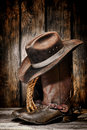 American west rodeo vintage cowboy boots dirty and used black felt hat atop worn and old leather working rancher with spurs and Stock Image