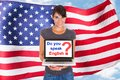 American woman asking do you speak english young holding laptop in front of usa flag Stock Photo