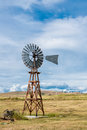 Americana vintage windmill a vertical image of a american on a grassy field and beautiful blue sky with wispy white clouds copy Stock Images