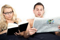Amicable couple reading in bed together with the wife concentrating on her book while her husband reads the latest news the Stock Photo