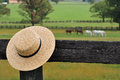 Amish straw hat hanging on a pennsylvania farm fence post Stock Image
