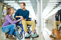 Amorous couple girl looking at her boyfriend in wheelchair in the mall Royalty Free Stock Image