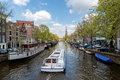 Amsterdam canal cruise ship with Netherlands traditional house i Royalty Free Stock Photo