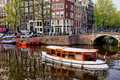 Amsterdam canal and houses city of in holland picturesque scenery boats on a historic terraced Royalty Free Stock Photo