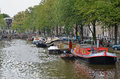 Amsterdam canal view of a in with moored houseboats Stock Images