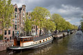 Amsterdam canal waterfront houseboats and apartment buildings on a in the city of netherlands Stock Photos