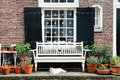Amsterdam, Holland, Europe - a building facade, a window, a white bench and a cat Royalty Free Stock Photo