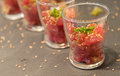 Amuse bouche of tuna tatar in glass sprinkled with roasted sesame seeds and spring onion Royalty Free Stock Images