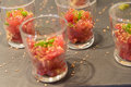 Amuse bouche of tuna tatar in glass sprinkled with roasted sesame seeds and spring onion Stock Image
