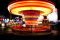 Amusement park at night ferris wheel and roundabout in motion Royalty Free Stock Photo