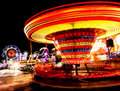 Amusement park at night ferris wheel and roundabout in motion Stock Photo