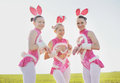 Amusing bunny outside bunnies three funny attractive females wearing costumes in field Stock Images