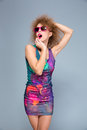 Amusing funny young woman in sunglasses posing on gray backgroung excited curly colorful dress and pink Stock Photo
